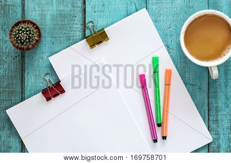 Blue Wooden Desk Table With Paper Reams, Cactus, Color Pen And Cup Of Coffee.