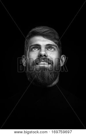 Black and white studio portrait of attractive bearded handsome young caucasian man with big smile over black background Happy mood and positive concept