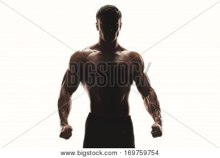 Dark silhouette of a strong man on white background. Confident young fitness man with strong hands and clenched fists. Creative concept. Clipping vactor path mask inside