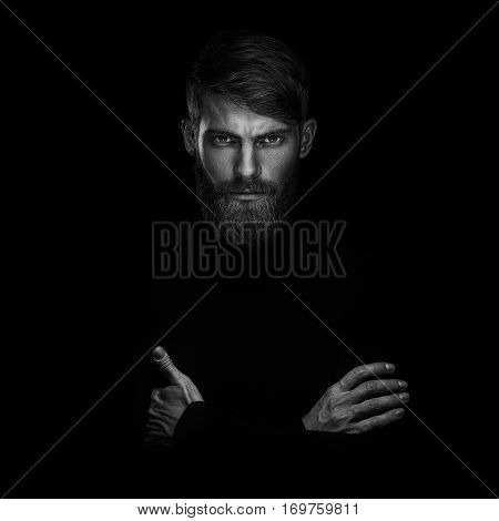 Portrait Of Serious Young Man With Arms Folded Standing Isolated On A Black Background And Looking A