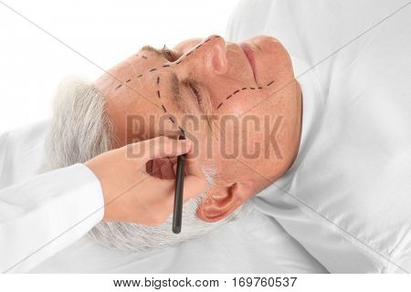 Female hand drawing correction line on man's face, close up