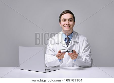 Young doctor with spectacles sitting at table on light background