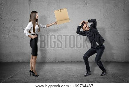Businesswoman on concrete background holding a carton box to a cowering man. Corporate world. Career path. Job requirements.