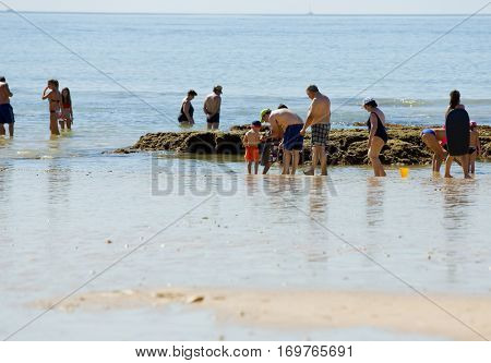 ALBUFEIRA, PORTUGAL - AUGUST 21, 2016: People at the famous beach of Olhos de Agua in Albufeira. This beach is a part of famous tourist region of Algarve.