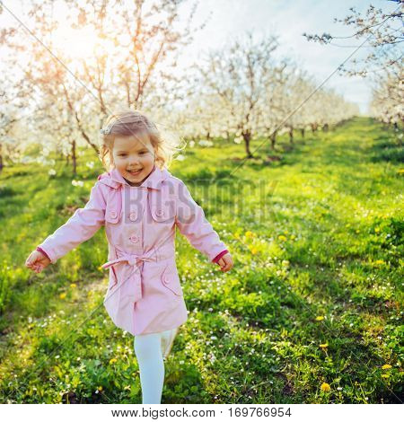 Little baby girl that runs between flowering trees at sunset. Art processing and retouching photos special.