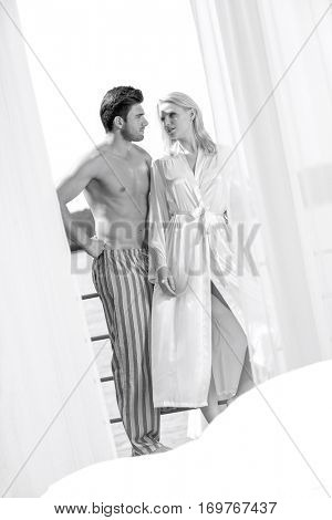 Young couple in sleepwear looking at each other on hotel balcony