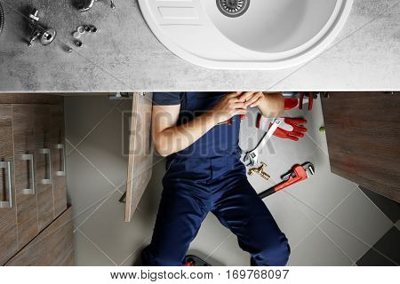 Male plumber repairing sink pipes in kitchen, top view