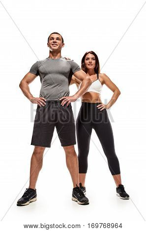 Smiling fitness couple standing together isolated on white background
