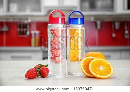 Bottles with fruit-infused water on kitchen table