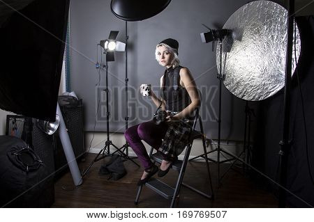 Female professional photographer dressed like a hipster or a millenial drinking coffee and taking a break. She is resting inside a photography studio thinking to be creative and artistic.
