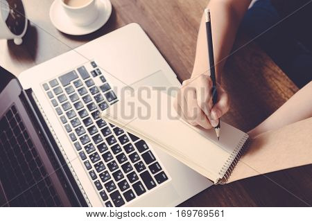 Female Writing Information On Paper In Workplace. Office Concept.