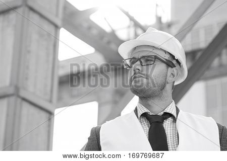 Young male architect wearing hard hat looking away at construction site