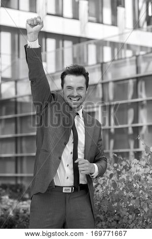 Portrait of excited businessman with arm raised celebrating success outside office building