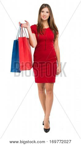 Full length portrait of a woman in red dress holding shopping bags