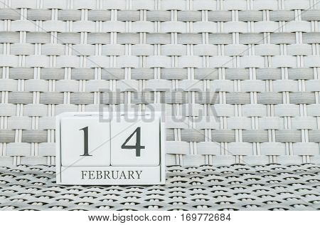 Closeup surface white wooden calendar with black 14 february word on blurred weave wood chair textured background with copy space in selective focus at the calendar