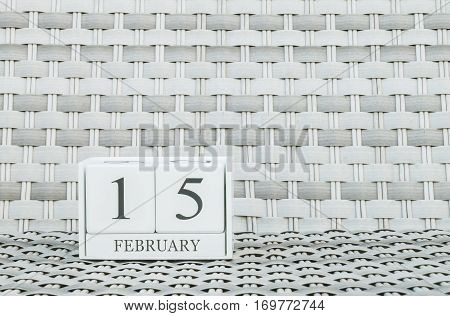 Closeup surface white wooden calendar with black 15 february word on blurred weave wood chair textured background with copy space in selective focus at the calendar