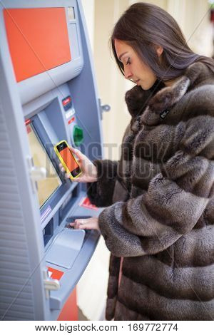 Young happy woman in mink fur coat withdrawing money from credit card at ATM