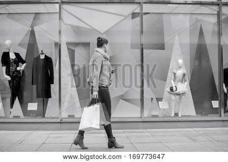 Profile shot of young woman with shopping bags looking at window display