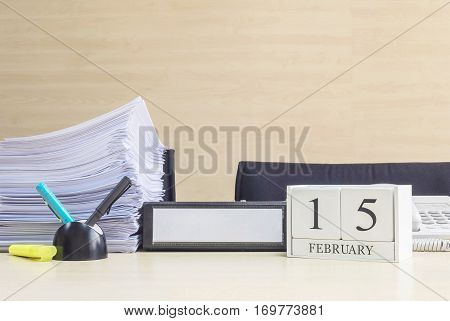 Closeup white wooden calendar with black 15 february word on blurred brown wood desk and wood wall textured background in office room view with copy space in selective focus at the calendar