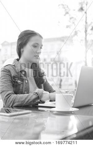 Woman using laptop at sidewalk cafe