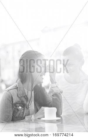 Happy women at sidewalk cafe during winter