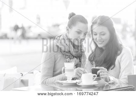 Happy women using cell phone at sidewalk cafe during winter