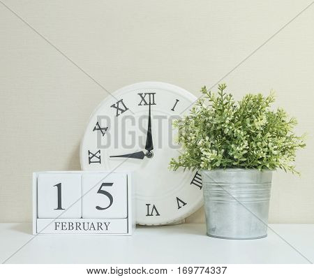 White wooden calendar with black 15 february word with clock and plant on white wood desk and cream wallpaper textured background in selective focus at the calendar