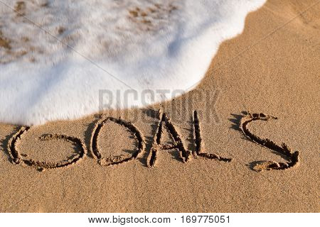 the word goals written in the sand of a beach and a wave of seawater