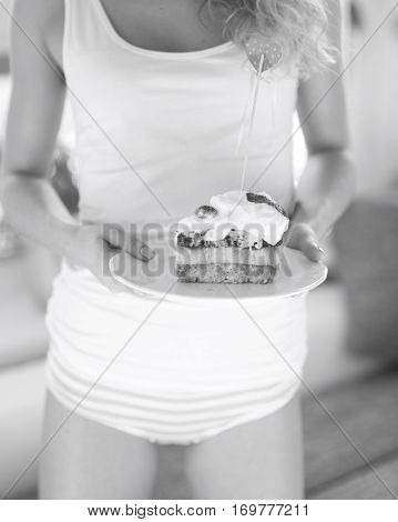 Mid section of woman with raspberry cake in house