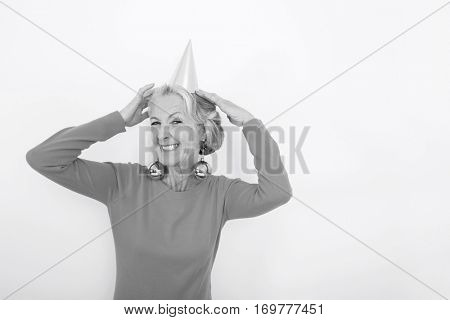 Portrait of senior woman wearing party hat and Christmas ornaments over white background