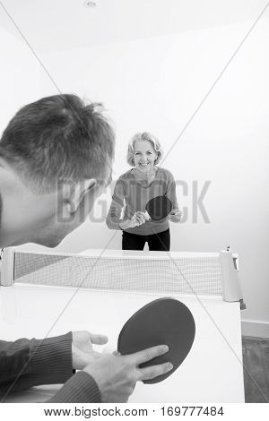 Portrait of senior woman playing table tennis in court