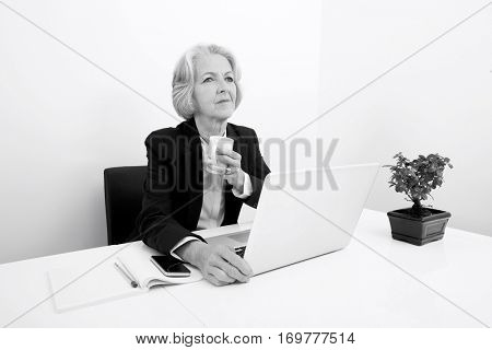 Thoughtful senior businesswoman having coffee at desk in office