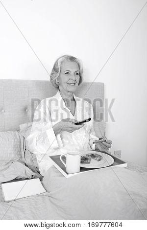Happy senior woman watching TV while having breakfast in bed