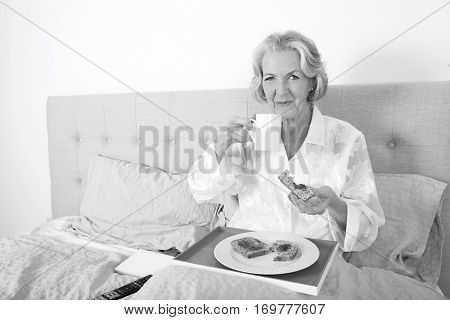 Portrait of senior woman having breakfast in bed