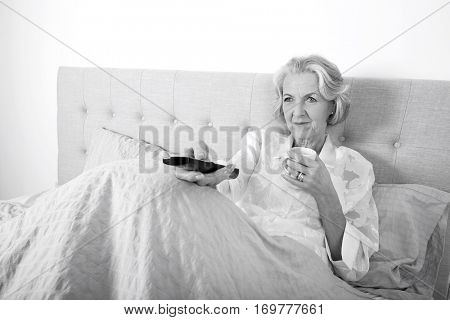 Senior woman watching TV while having coffee in bed
