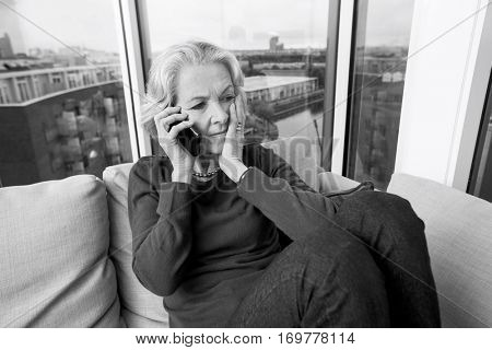 Worried senior woman answering smart phone on sofa at home