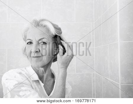 Portrait of senior woman brushing hair in bathroom