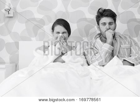 Young couple suffering from cold and flu in bed at home