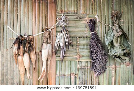 drying cereal corn vegetable cotton leaf bush with forest product hanging on bamboo rattan pannel background show rural agriculture life