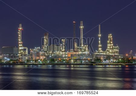 Night scene of oil refinery plant of Petrochemistry industry in twilight time and reflection in near river in Bangkok Thailand.