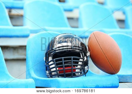 Rugby helmet with ball on stadium chair