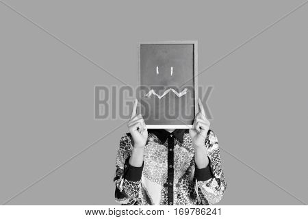 Teenage boy holding slate with confusion smiley on it over red background