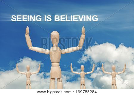 Wooden dummy puppet on sky background with words SEEING IS BELIEVING. Abstract conceptual image