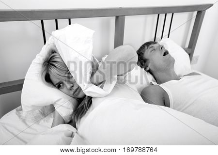 Frustrated woman covering ears with pillow while man snoring in bed