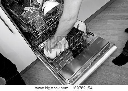 Cropped image of man loading dishwasher in kitchen