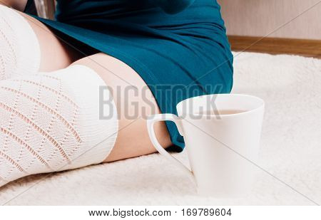 White cup of tea close to girl's legs in white stockings and green dress
