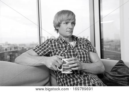 Thoughtful mid-adult man sitting with coffee cup in living room at home