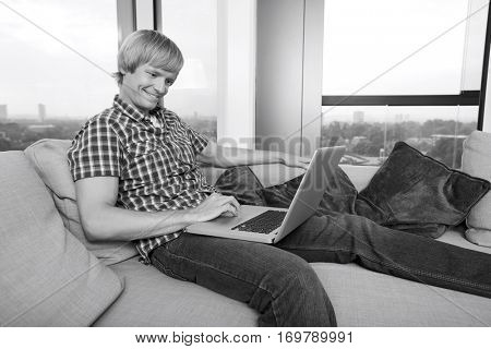 Side view of smiling mid-adult man using laptop on sofa at home