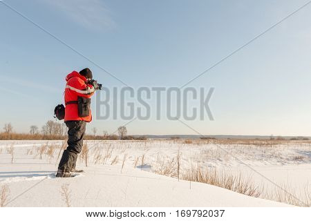 photographer takes winter landscape at dawn in the bitter cold.