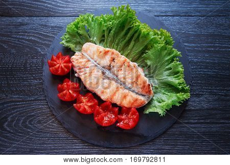Plate with grilled fish and vegetables on dark wooden table